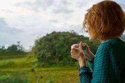 Vrouw in landschap met kop koffie